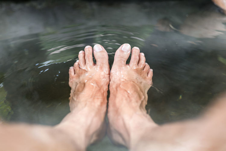 Low section of person relaxing in hot water spring lake