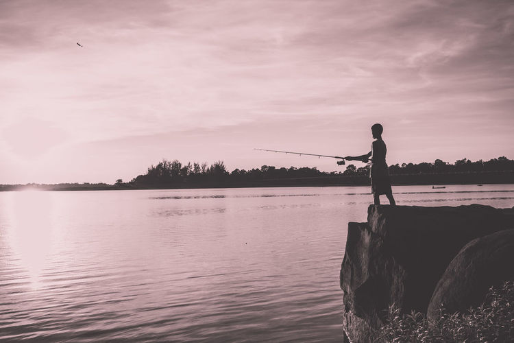 Silhouette of man standing on calm lake