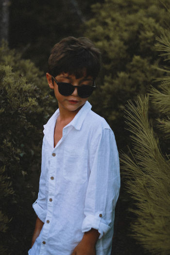 Boy wearing sunglasses standing against plants