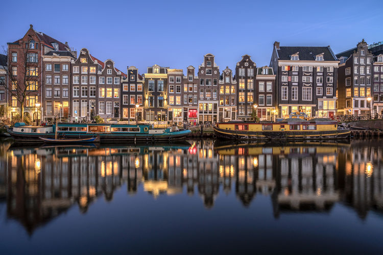 Beautiful Amsterdam canal reflections, just after sunset. Amsterdam Architecture Building Exterior Canal Canal Houses City Cityscape Clear Sky Illuminated Nautical Vessel No People Outdoors Reflection Scenics Tourism Travel Destinations Water Dutch Netherlands Amsterdamse Grachten Amsterdam Canal Amsterdamcity Paint The Town Yellow