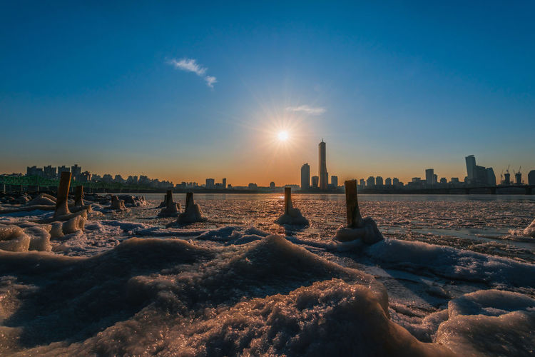 Evening sunset at the Han River in winter South Korea Architecture Beauty In Nature Bright Building Building Exterior Built Structure City Cityscape Cold Temperature Land Landscape Lens Flare Nature No People Office Building Exterior Scenics - Nature Sky Skyscraper Snow Sun Sunbeam Sunlight Sunset Water Winter