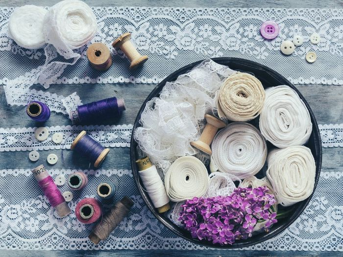 Directly Above View Of Sewing Items With Purple Lilac Flowers On Table
