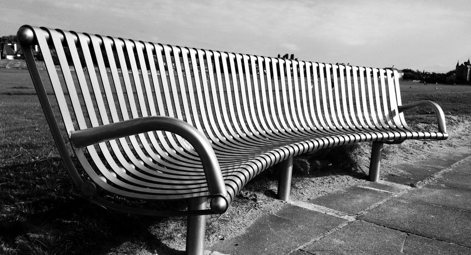 Empty bench with chairs in background
