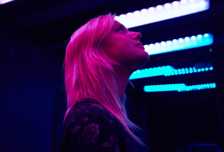 Pink light falling on smiling young woman in illuminated room