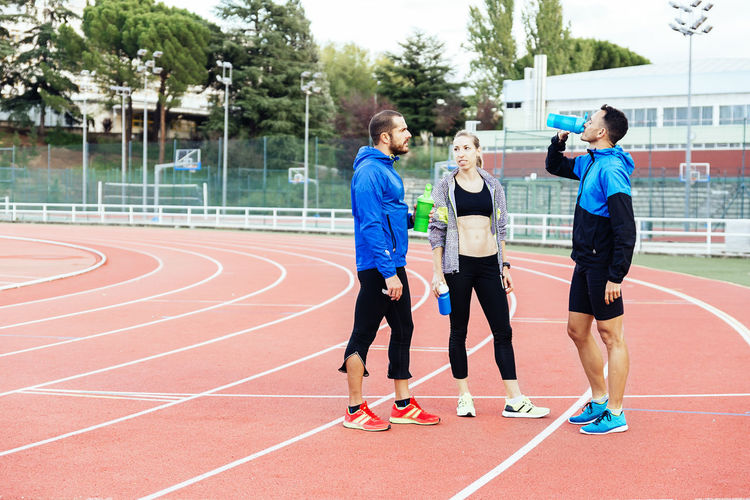 Full length of people standing on running track
