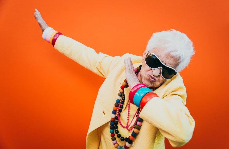 Portrait of stylish senior woman wearing colorful jewelry dancing against orange background