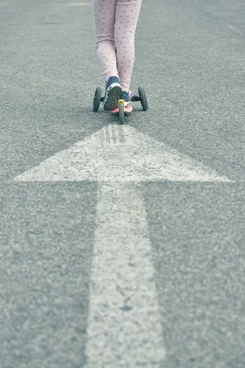 Low section of woman skateboarding on road