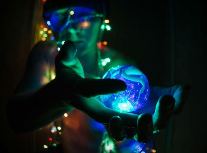 Shirtless man holding illuminated lights