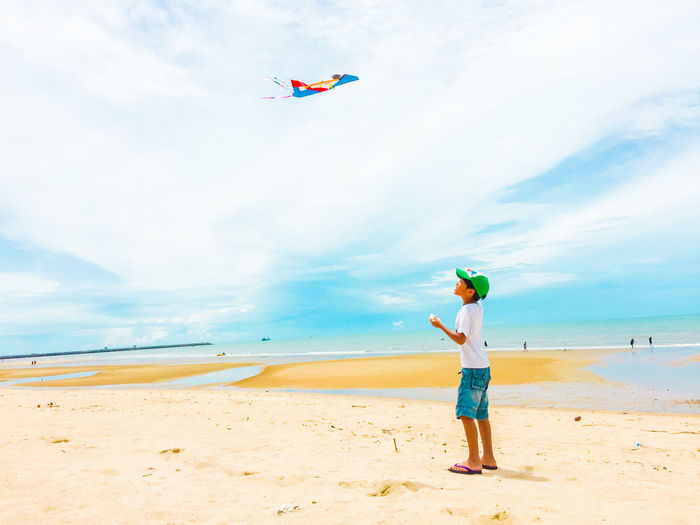 Low angle view of boy flying over beach against sky
