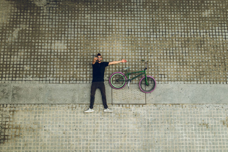 Side view of woman with bicycle standing against wall