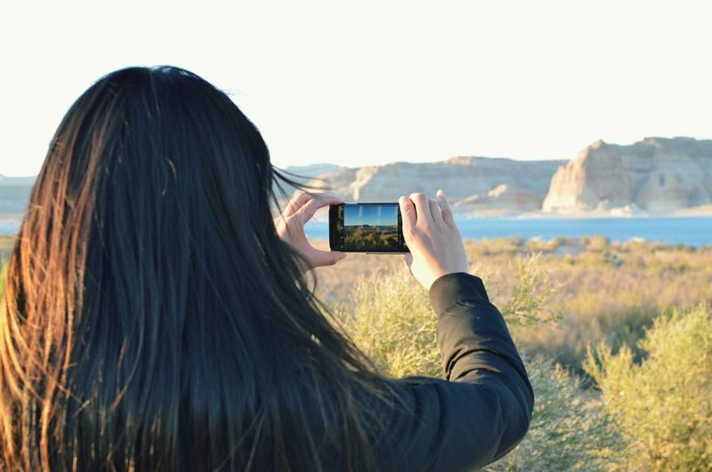 Rear View Of Woman Photographing Lake Through Smart Phone