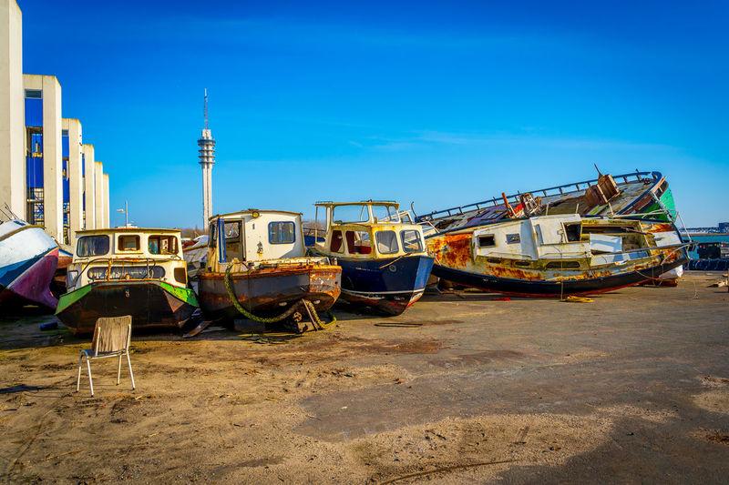 Boats moored on beach against clear blue sky