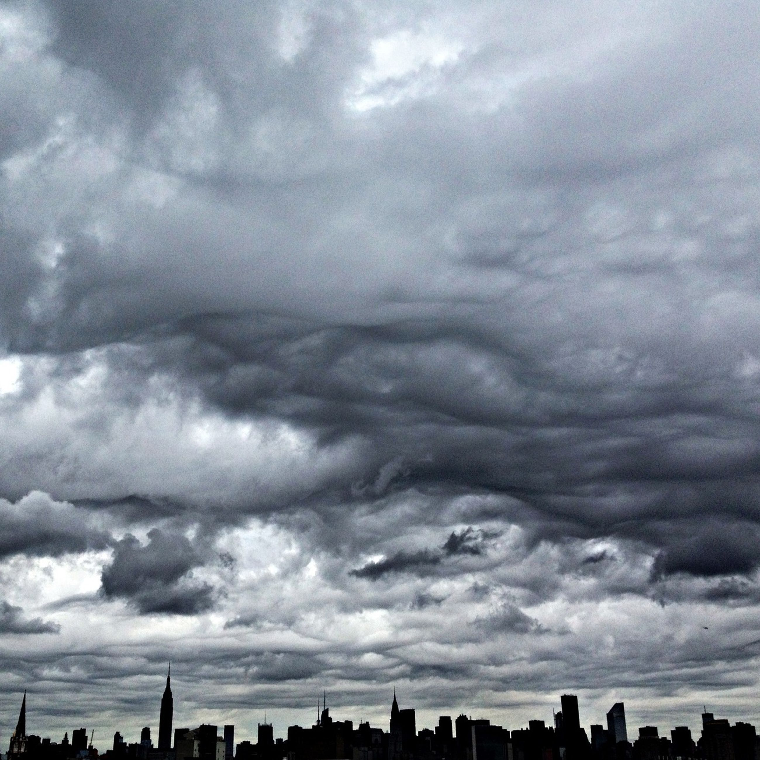 sky, cloud - sky, cloudy, building exterior, architecture, built structure, city, weather, cityscape, overcast, cloud, storm cloud, cloudscape, skyscraper, nature, silhouette, low angle view, outdoors, scenics, urban skyline