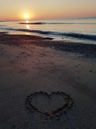 Heart shape on beach against sky during sunset