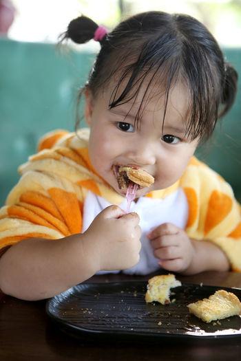 Portrait of cute baby eating food