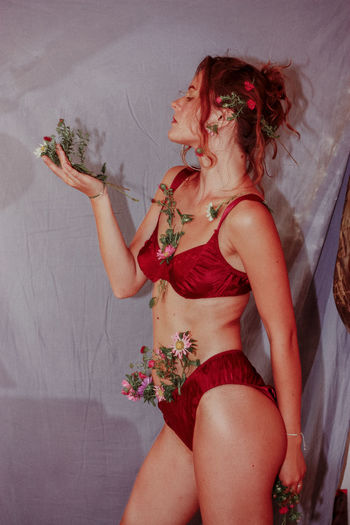 Midsection of woman with pink flower