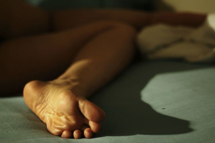 Low Section Of Woman Resting On Bed