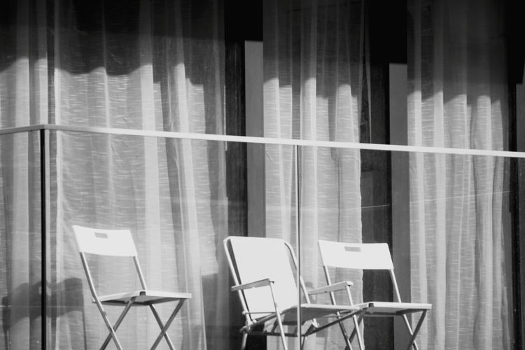 Empty chairs and tables on balcony
