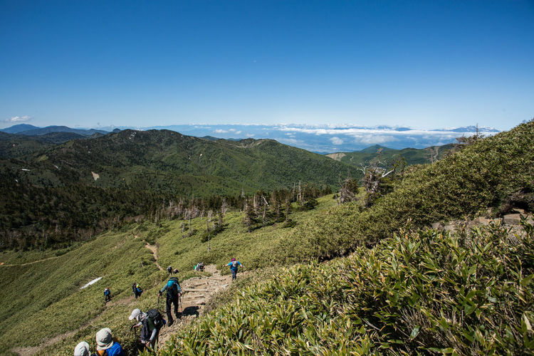 High angle view of people on mountain against clear blue sky