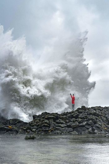 Man Standing On Rock By Splashing Sea Wave Against Sky