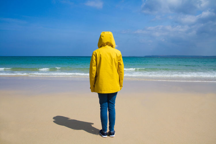 Rear view of woman wearing yellow hooded jacket at beach against sky on sunny day