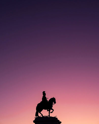 Silhouette statue against clear sky during sunset