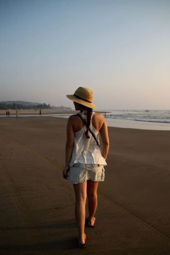 Back View Of Girl Beach Beach Life Beach Photography Full Length Goa Hat Headwear India Nature North Goa Ocean One Person One Woman Only One Young Woman Only Outdoors Sea Summer Sun Hat Vacations Walking On The Beach Water Young Women