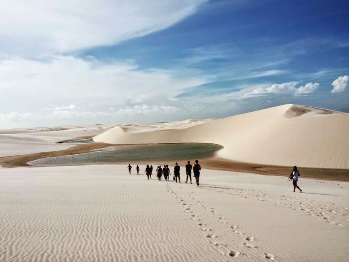 People Walking On Sand Dune In Desert