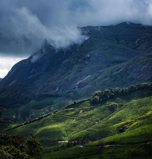 Rain clouds looming over mountain ranges with tea plantation below