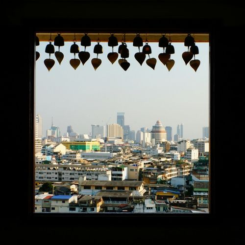 Cityscape Through Window Bangkok From Golden Mount Urban Skyline No People From The Inside Looking Out Hanging Hearts Scyscrapers In The Background Old And New Architecture Travel Destinations Sony A6000 No Photoshop Wind Bells Frame It!
