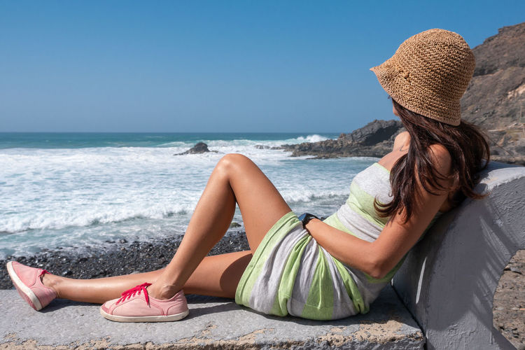 Sea Water Hat Beach Land Relaxation Leisure Activity Adult Women Vacations Holiday Nature Trip Lying Down One Person Young Adult Sky Sitting Casual Clothing Clothing Horizon Over Water Hairstyle Outdoors