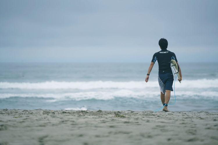 Rear view of man walking on beach