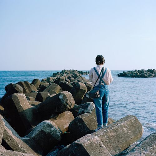 Rear view of woman standing on groyne in sea against clear sky