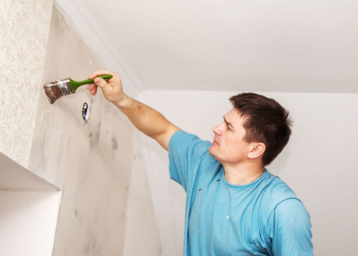 Painter working at incomplete home
