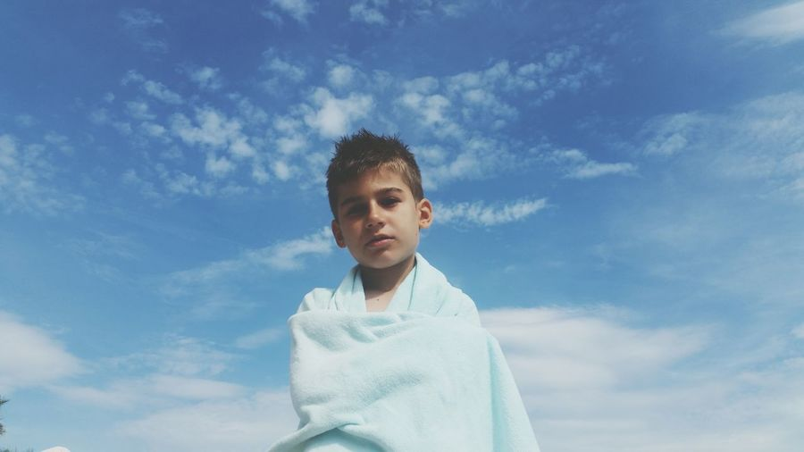 Low angle portrait of boy with towel standing against sky