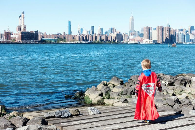Superboy... City Urban Skyline Building Exterior Full Length Water Cityscape Architecture Rear View Childhood One Person Outdoors Standing Built Structure Travel Destinations Children Only Skyscraper People Day Williamsburg An Eye For Travel
