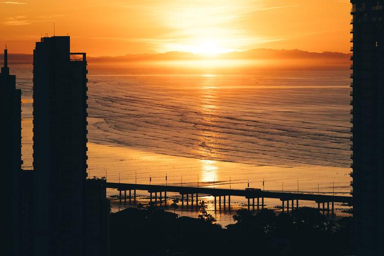 Silhouette building by sea against orange sky