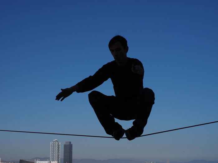 Low angle view of silhouette man performing stunt on rope against clear blue sky