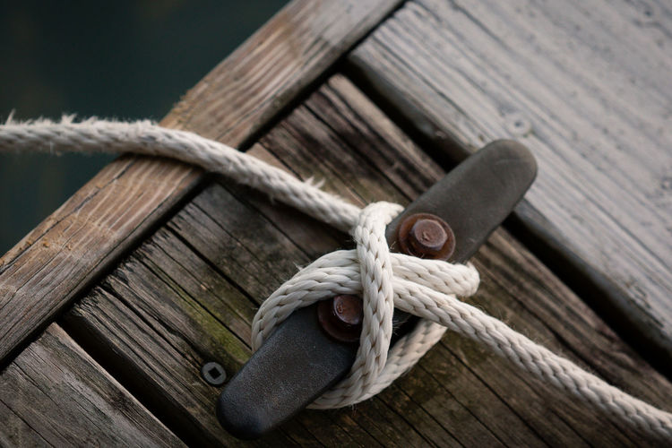 High angle view of rope tied up of cleat on pier