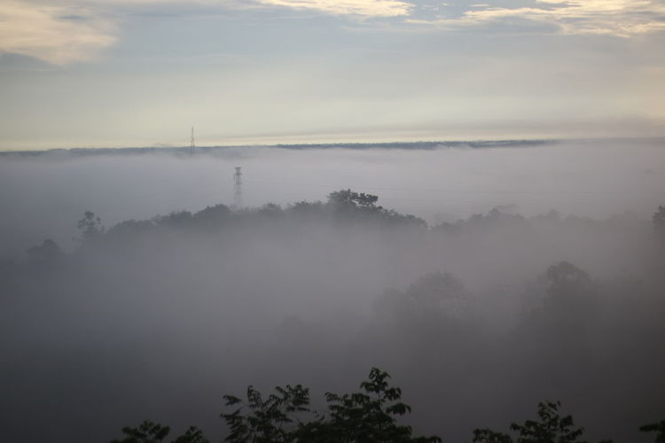 Scenic view of fog covered landscape against sky