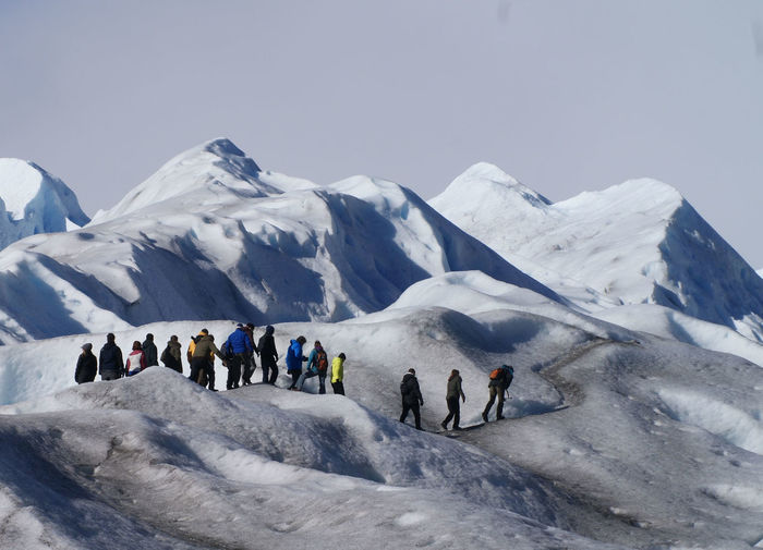 Hikers on snowcapped mountain against sky