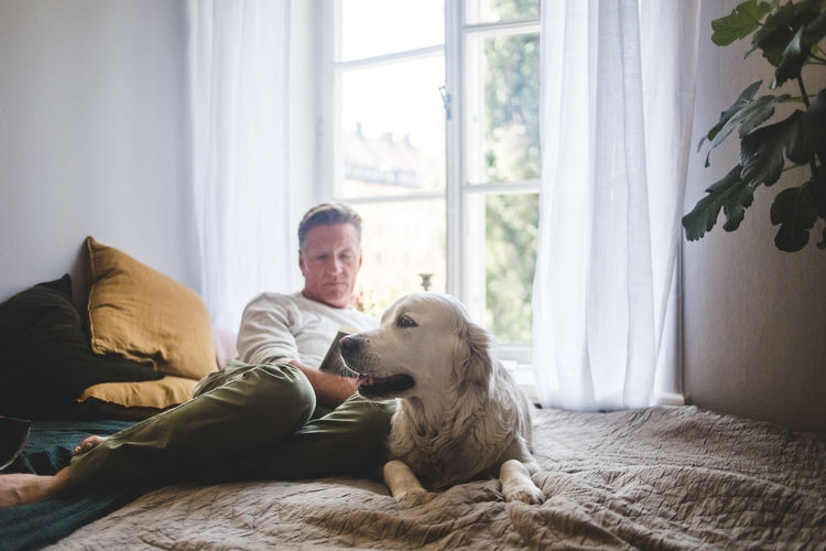 Man with dog sitting at home
