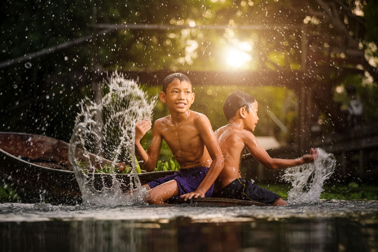 Happy shirtless boys splashing water while sitting on boat in river