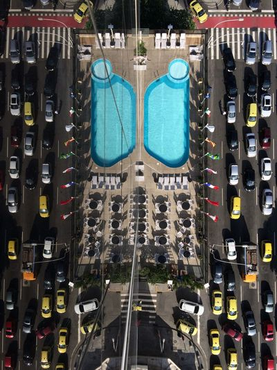 Reflection Of Tourist Resort And Cars On Glass Building