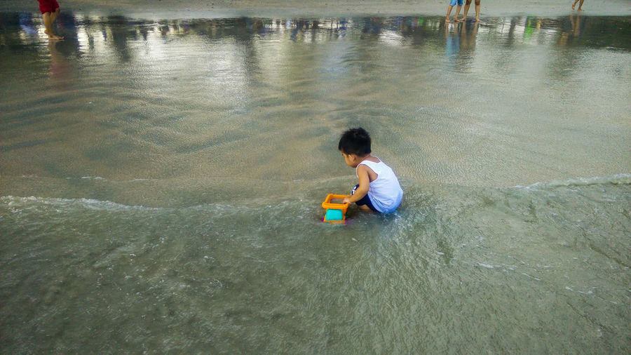 High angle view of boy playing at beach