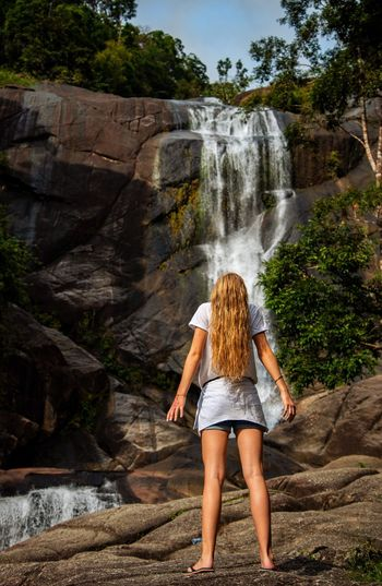 Rear view of woman standing on rock against waterfall