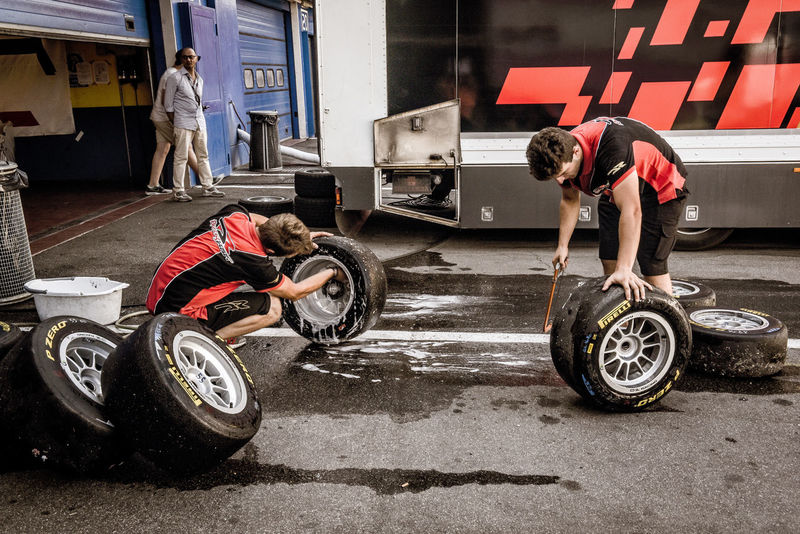 Two mechanics washing and clening racing cars tires set in the pit Auto Repair Shop Car Circuit Cleaning Day Editorial Use Only Mechanics Motor Sport Occupation People Race Racing Racing Car Racing Tire Real People Set Tire Track Washing Working