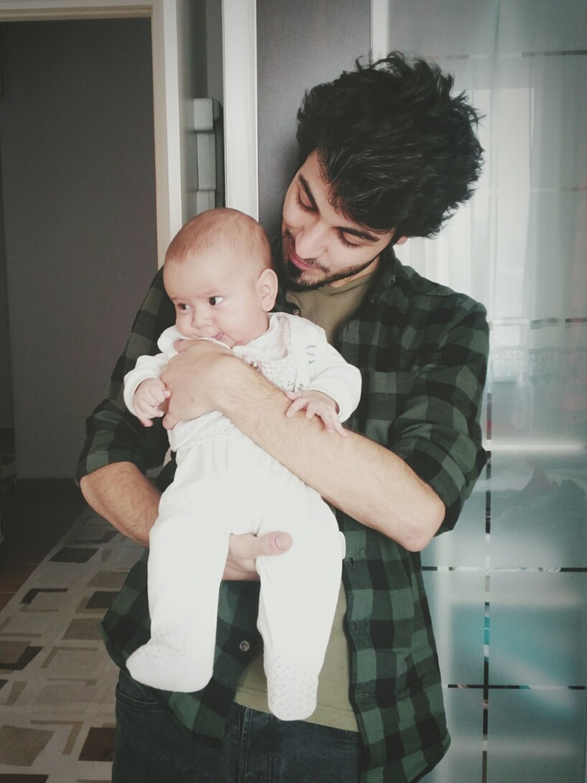 baby, real people, togetherness, love, family with one child, lifestyles, family, holding, bonding, babyhood, young adult, indoors, childhood, young men, casual clothing, home interior, front view, father, son, leisure activity, new life, care, happiness, young women, day, men, people