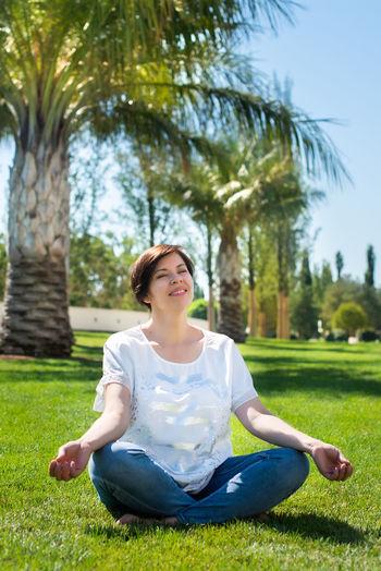 Full length of woman meditating while sitting at park