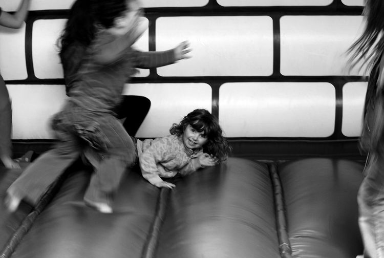 Portrait Of Girl Playing With Friends On Bouncy Castle